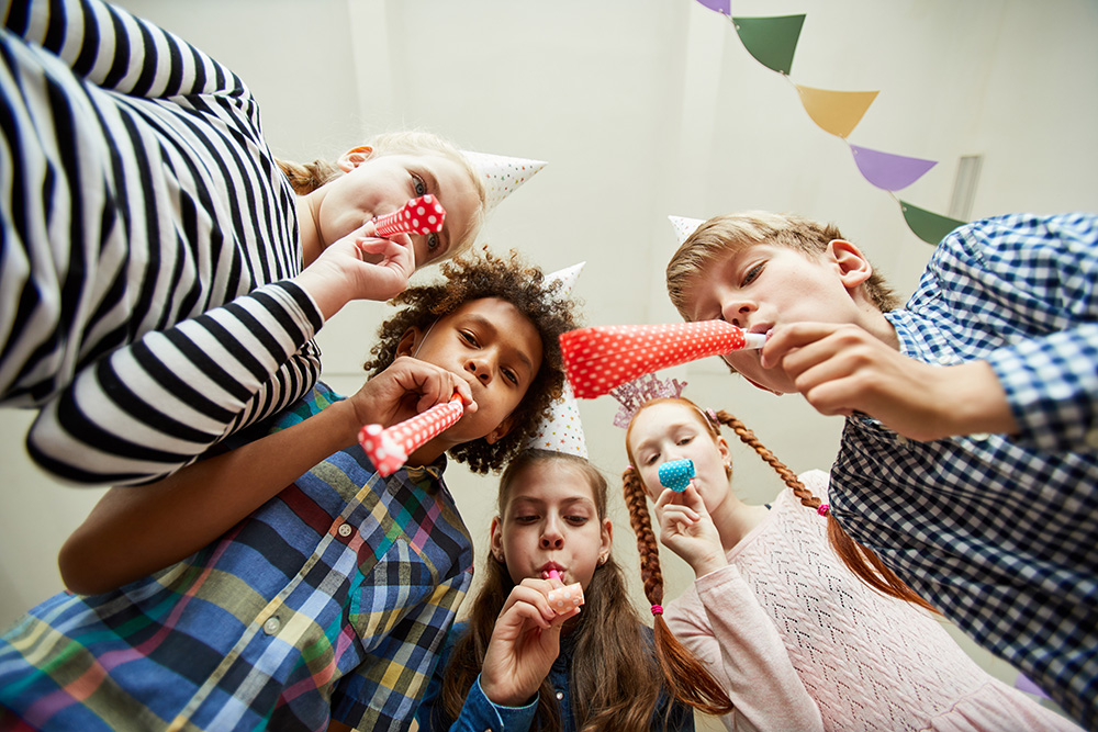 Group of Children Blowing Party Horns